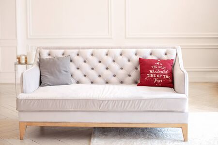 Pillow with Christmas decoration on a beige sofa in interior of room. Modern minimalist living room interior with sofa against a white wall. Spacious classic style living room with a velvet sofa.