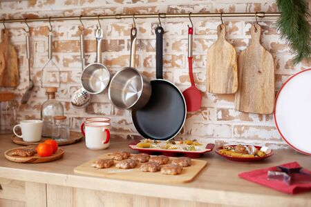 Bright kitchen interior with red decor and christmas decorations. Cooking a festive dinner at home in kitchen concept. Christmas gingerbread cookies on a wooden board. Hanging utensils on a brick wall Archivio Fotografico - 138047465