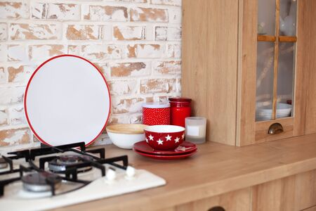 Christmas decor and decorations in kitchen. Christmas tableware. Christmas cooking utensils. Bright interior of New Year kitchen with red decor. Kitchen utensils, plates on table in rustic kitchen. Reklamní fotografie