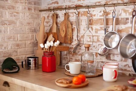 concept organizing kitchen. Attic dining room design and rustic cuisine. Brick wall with shelves with hooks, chopping wooden boards, banks, cups. Kitchen utensils on modern countertop of home cooking. Archivio Fotografico - 138047658