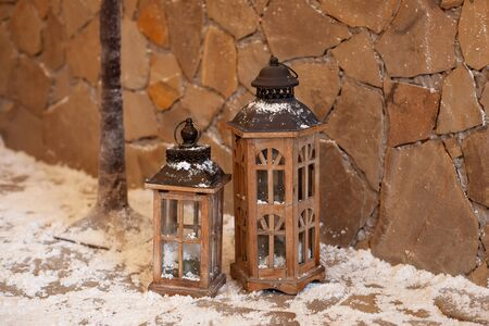 vintage lanterns outdoors on doorstep in european old house on christmas eve. porch of house is decorated with wooden lanterns. Old lantern on a rustic stone threshold. Christmas home decor. New year