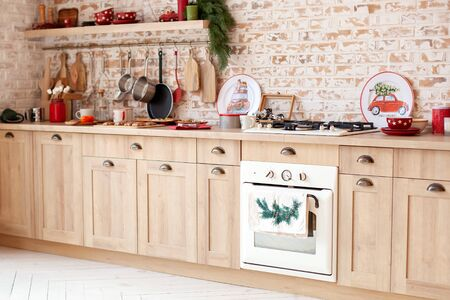 Modern kitchen furniture on a brick wall background. Christmas kitchen interior. Scandinavian design. organization of the kitchen. Rustic kitchen with furniture, wooden worktop and oven, pots, plates.