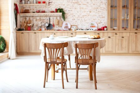 Stylish kitchen interior with wooden table and chairs. Wooden dining table for 4 people. Stylish kitchen interior. Rustic kitchen interior. Scandinavian dining room in cottage style. Eco furniture Reklamní fotografie