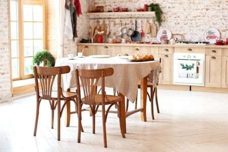 Bright spacious dining room with large wooden oval table. room with a wooden dining table, chairs and a kitchen in a modern house. Wooden furniture and decorations in rustic living room. Scandinavian