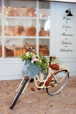Vintage yellow bike with a basket with flowers stands near the cafe of a bakery against the background of the wooden blue house. Summer mood. Eco transport. bicycle with flower pot, wedding flower Reklamní fotografie