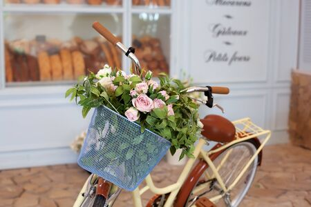 Beautiful romantic landscape: vintage wicker basket with flowers near the cafe. Old bicycle with flowers in a metal basket on the background of a bakery or coffee shop against the blue wall.