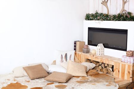 Stylish scandinavian minimalistic interior with an elegant sofa. Comfort home. Modern country house interior with wooden bed, firewood, fireplace. christmas decor in a room idoor. New year Reklamní fotografie