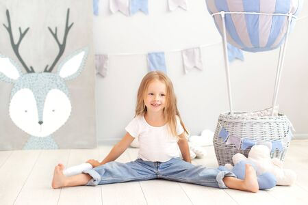 Little blonde girl in a T-shirt and jeans sits near a decorative ball. Funny kid plays near the ball in the children's room. The concept of childhood, creativity. birthday, holiday decorations Stock Photo