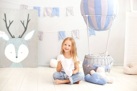 A little girl in casual clothes holds a cloud pillow against the background of a decorative ball. The child plays in the children's room. The concept of childhood. birthday, holiday decorations