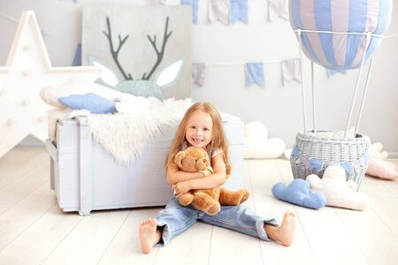Smiling little blond girl hugs a teddy bear on the background of a decorative ball. The child plays in the children's room with toys. The concept of childhood, travel. birthday, holiday decorations
