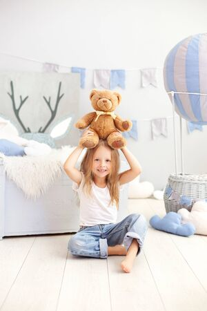 Little blond girl holding a teddy bear on the background of a decorative ball. The child plays in the children's room with toys. The concept of childhood, travel. Toddler in kindergarten. interior