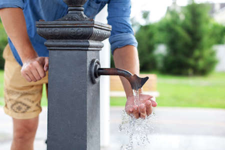 Man washing his hand in faucet water. Ð¡ity water tap with drinkable water in park. Drinking column. Ancient black column for distribution of drinking water installed on street. Watertap on hydrant