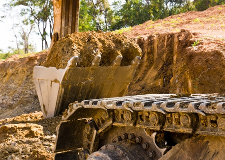 Back hoe standing in mining with raised bucket full of sand Stock Photo - 9141546