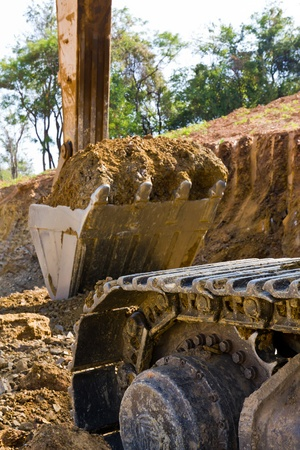 Back hoe standing in mining with raised bucket full of sand Stock Photo - 9141542