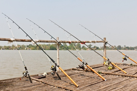 Fishing Poles on Pier with river in Background Stock Photo - 9393451