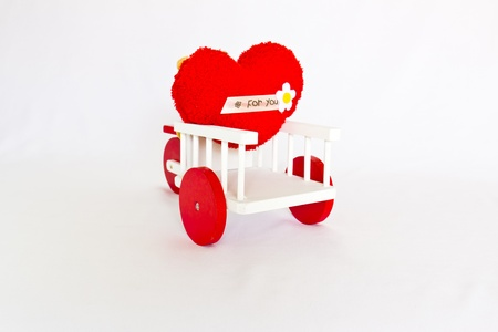 Red heart on a tricycle. photo