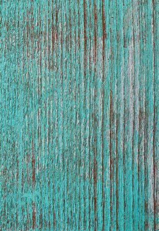 Green paint peeling from a wooden panel door showing the wood grain photo