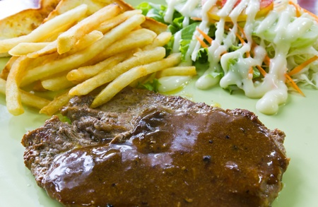 Steak with fresh vegetables salad and french fries photo