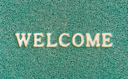 Green door mat with welcome written on it photo