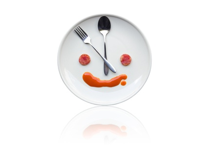 human like: Metal spoon and fork arrange as clock face on white dish with artistic human like face from food