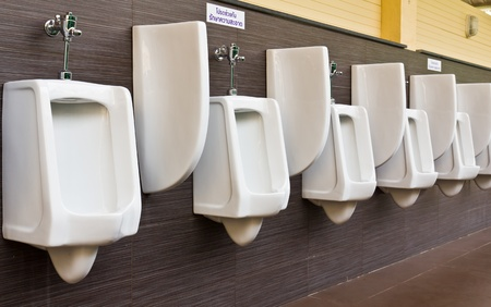 Row of white porcelain urinals in public toilets photo