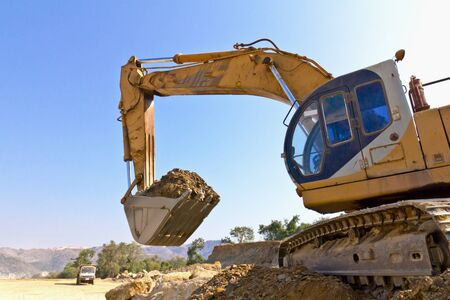 back hoe: The back hoe is lifting and moving dirt.Back hoe vehicle on a pile of dirt