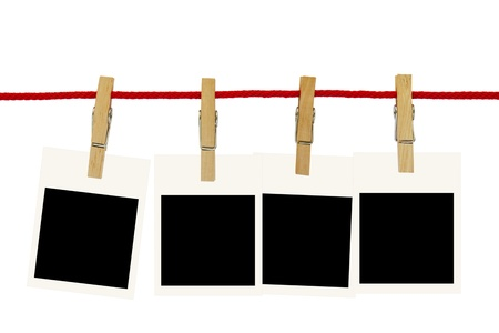 Blank photo frames hang by wooden peg on white background