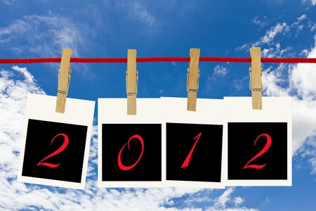 Photo frames 2012 and blue sky hang by wooden peg on white background Stockfoto