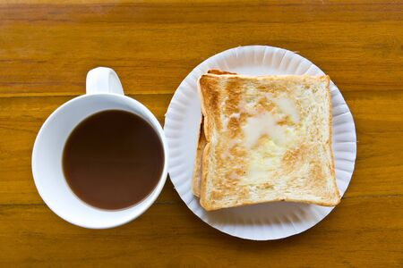 Coffee cup and Pour the milk toast on the wooden table photo
