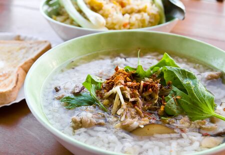 Asian style rice soup with herbs in a bowl