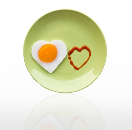 Fried egg heart and source heart on green dish