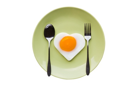 Fried egg heart and spoon on green dish