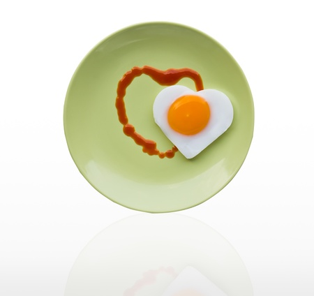 Fried egg heart and sauce heart on green dish