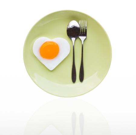 huevos fritos: Coraz�n huevo frito y una cuchara en el plato verde