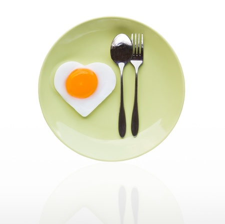 Fried egg heart and spoon on green dish photo