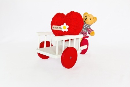 Red heart and bear on a tricycle. photo