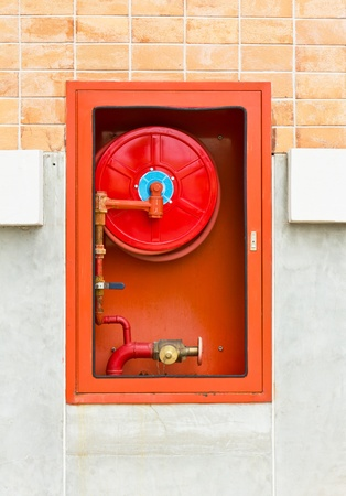 Hydrant with water hoses and fire extinguish equipment on wall photo
