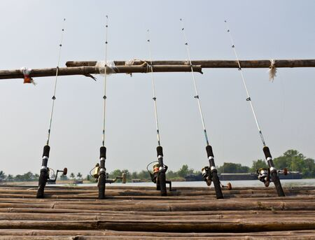 Fishing Poles on Pier with river in Background photo