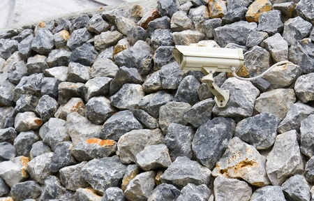 CCTV camera against on rock wall photo