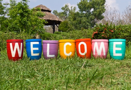 Clay pots and painting with welcome message Stock Photo