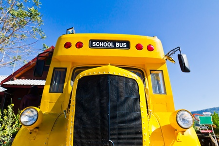Yellow school bus against blue sky photo
