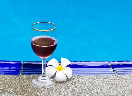 Red wine glasses and flower at the pool  Relaxing scene