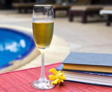 Wijnglazen en boek bij het zwembad Ontspannen scène Stockfoto - 13209775