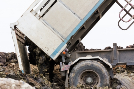 camion volquete: Vuelca cami�n de dumping y el suelo de tierra en el sitio de construcci�n