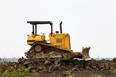 Bulldozer machine doing earth moving work in construction site Stock Photo - 16027249