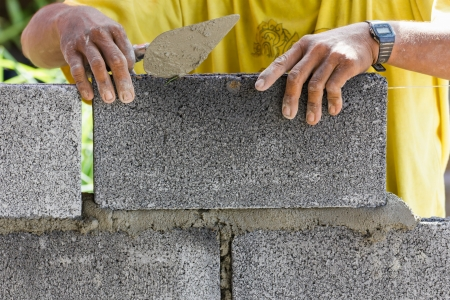 manual job: Bricklayer putting down another row of bricks in site