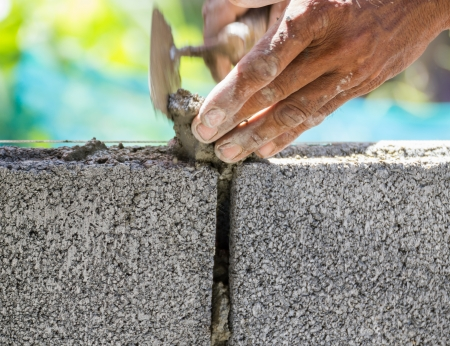 Bricklayer putting down another row of bricks in site Stock Photo - 16231857