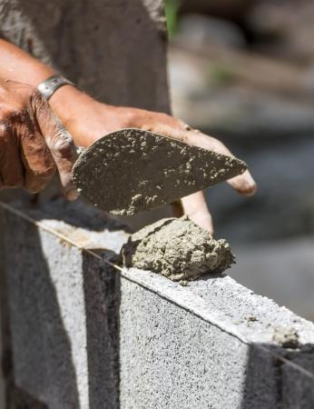 bricklayer: Alba�il echando otra fila de ladrillos en el sitio