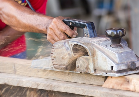 Carpenter working with electric planer  in his workshop, close up on the tool with hands photo