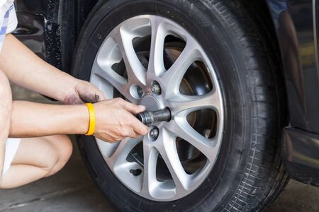 Replacing lug nuts by hand while changing tires on a vehicle Stock Photo - 18153003